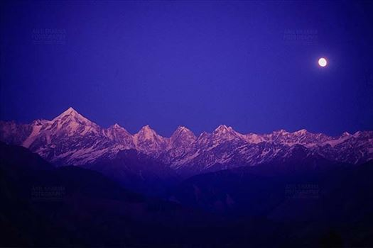 Mountains- Panchchuli Peaks (India) - Pink color Panchchuli Peaks and full moon in the blue sky, view from Munsyari at Uttarakhand, India.
