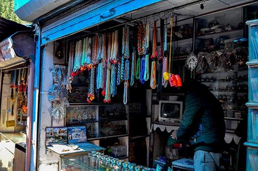 Gangotri, Uttarakhand, India- May 13, 2015: Shops to buy necklaces, beads, jewelry, gemstones, bracelets, earrings, bangles, and devotional objects for religious ceremonies at Gangotri Bazaar, Uttarkashi, Uttarakhand, India.