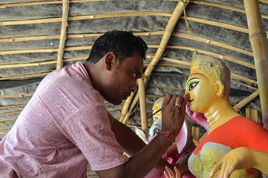 Durga Puja Festival, Noida, Uttar Pradesh, India- September 21, 2017: An artist from West Bengal  giving final touches to the eyes of Goddess Durga's idol at Noida, Uttar Pradesh, India.